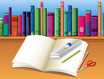 An empty notebook in front of the wooden shelf with books Stock Photo