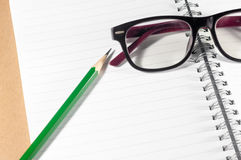 Empty notebook with green pencil, eyeglasses and lined page Stock Photo