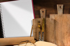 Empty Notebook in the Kitchen. With copy space, cutting boards, silver cutlery, recipe book, eyeglasses and rolling pin Royalty Free Stock Image
