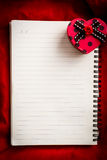 Empty notebook with lined page and heart shape gift box on red f Stock Image