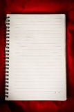 Empty notebook with lined page on red fabric. Stock Photo