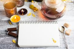 Empty notebook with lit candles and tea pot stock image