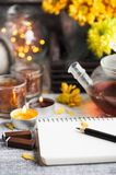 Empty notebook with lit lights and tea pot stock photos