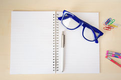 Empty notebook with office accessories and  blue frame eye glasses Stock Photography