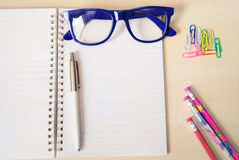 Empty notebook with office accessories and  blue frame eye glasses Stock Photos