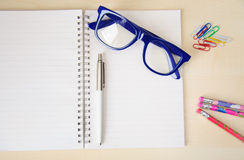 Empty notebook with office accessories and  blue frame eye glasses Royalty Free Stock Image