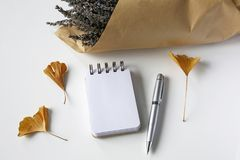 Empty notebook, pen, ginkgo leaves, lavender flowers on white. Table royalty free stock photography