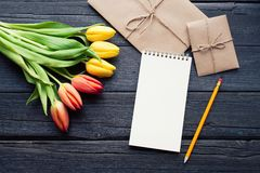 Empty notebook, pencil and yellow and red tulips flowers on vintage wooden background. Selective focus. Place for text. Flat lay stock photos