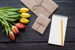 Empty notebook, pencil and yellow and red tulips flowers on vintage wooden background. Selective focus. Place for text. Flat lay Stock Images