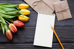Empty notebook, pencil and yellow and red tulips flowers on vintage wooden background. Selective focus. Place for text. Flat lay Royalty Free Stock Image