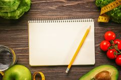 Empty notebook and set of healthy food. On wooden table Stock Photo