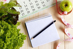 Empty notebook with vegetable salad and apple Royalty Free Stock Photography