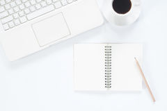 Empty notebook with white computer laptop and coffee cup Royalty Free Stock Images