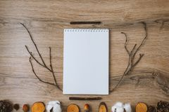Empty notebook on a wooden background, decorated with twigs and acorns. place for text stock photos