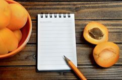 Empty notepad and apricots Stock Images