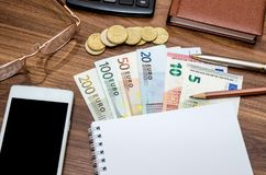 Empty notepad with euro money, mobile, calculator and pen. On table Stock Photo