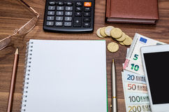 Empty notepad with euro money, mobile, calculator and pen Stock Images