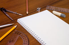 Empty notepad, pen, pencil, ruler, compass on dark wooden background Royalty Free Stock Images
