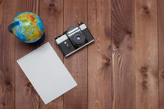 Empty notepad, retro camera and globe on brown wooden background. Travel concept - empty notepad, retro camera and globe on brown wooden background. Prepare for Royalty Free Stock Images