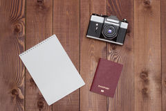 Empty notepad, retro camera and passport on brown wooden background. Travel concept - empty notepad, retro camera and passport on brown wooden background Royalty Free Stock Photography