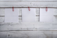 Empty notepads hanging on ribbon, paper clips Royalty Free Stock Photo