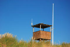 Empty Observing Stand On Beach. Wooden stand and flagpost against blue sky behind dune Royalty Free Stock Photography