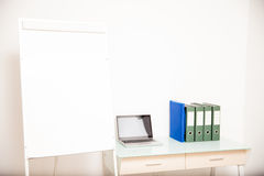 Empty office with a blank flip chart Royalty Free Stock Photos