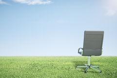 Empty office chair on green grass and blue sky Stock Photography