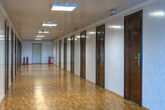 Empty office corridor with many doors of dark red  wood. Long office hallway with many doors of dark red wood Stock Images