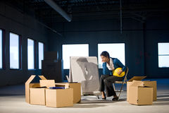 Empty office space. Young woman in empty office space with moving boxes Royalty Free Stock Images