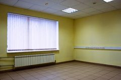 Empty office window. Corner of empty office room with floor of stones, ceiling, lamps, yellow walls, window with jalousie closed and  radiator for panel heating Royalty Free Stock Photo