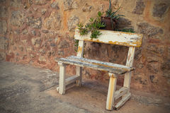 Empty Old Bench. Empty Rustic wooden outdoor cottage bench painted white against wall royalty free stock photo