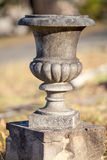Empty old concrete or stone urn on a small plinth Royalty Free Stock Photos