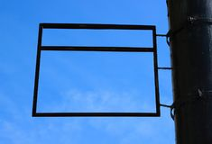 A blank rectangular advertising sign framing a blue sky background. royalty free stock images