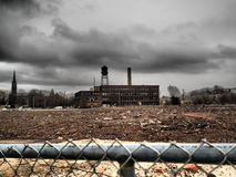 Empty Old Factory Building Under Ominous Sky. An empty old factory building under ominous sky in landscape of rural urban decay Stock Photo