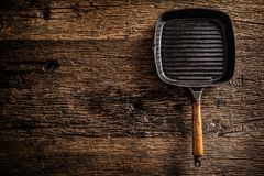 Empty old grill pan on rustic oak table - top of view stock image