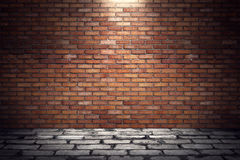 Empty old grungy room with red brick wall and paving stone floor Royalty Free Stock Photos