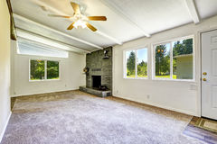 Empty old house interior with fireplace. Bright empty living room with fireplace and carpet floor. Old house interior Stock Image