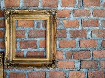Empty old ornate golden frames hanging on brick wall royalty free stock photography