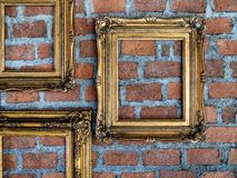 Empty old ornate golden frames hanging on brick wall. Three empty old ornate golden frames hanging on brick wall stock images