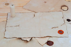 Empty old paper and candle-end. On the table a lot of things for notes Stock Photography