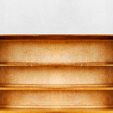 Empty old retro wooden book shelf. Near the stucco wall Royalty Free Stock Photo