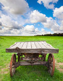 Empty old rural wooden cart stands on green field Stock Photo