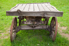 Empty old rural wooden wagon on green grass Royalty Free Stock Image