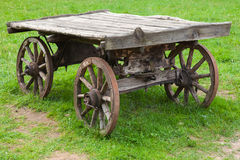 Empty old rural wooden wagon on green summer grass Royalty Free Stock Photography