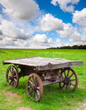 Empty old rural wooden wagon stands on field Stock Images