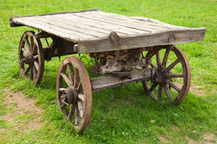 Empty old rural wooden wagon stands on grass Stock Photography