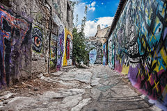 Empty old street covered with graffiti. Empty old lane with cracked road and walls covered with colorfull graffiti royalty free stock images