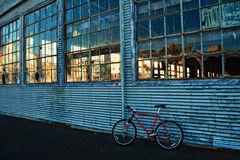 Empty old warehouse with broken glass, bike leaning on the wall Royalty Free Stock Photos