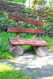 Empty old wooden bench on a green lawn. Garden or park, outdoors Stock Image